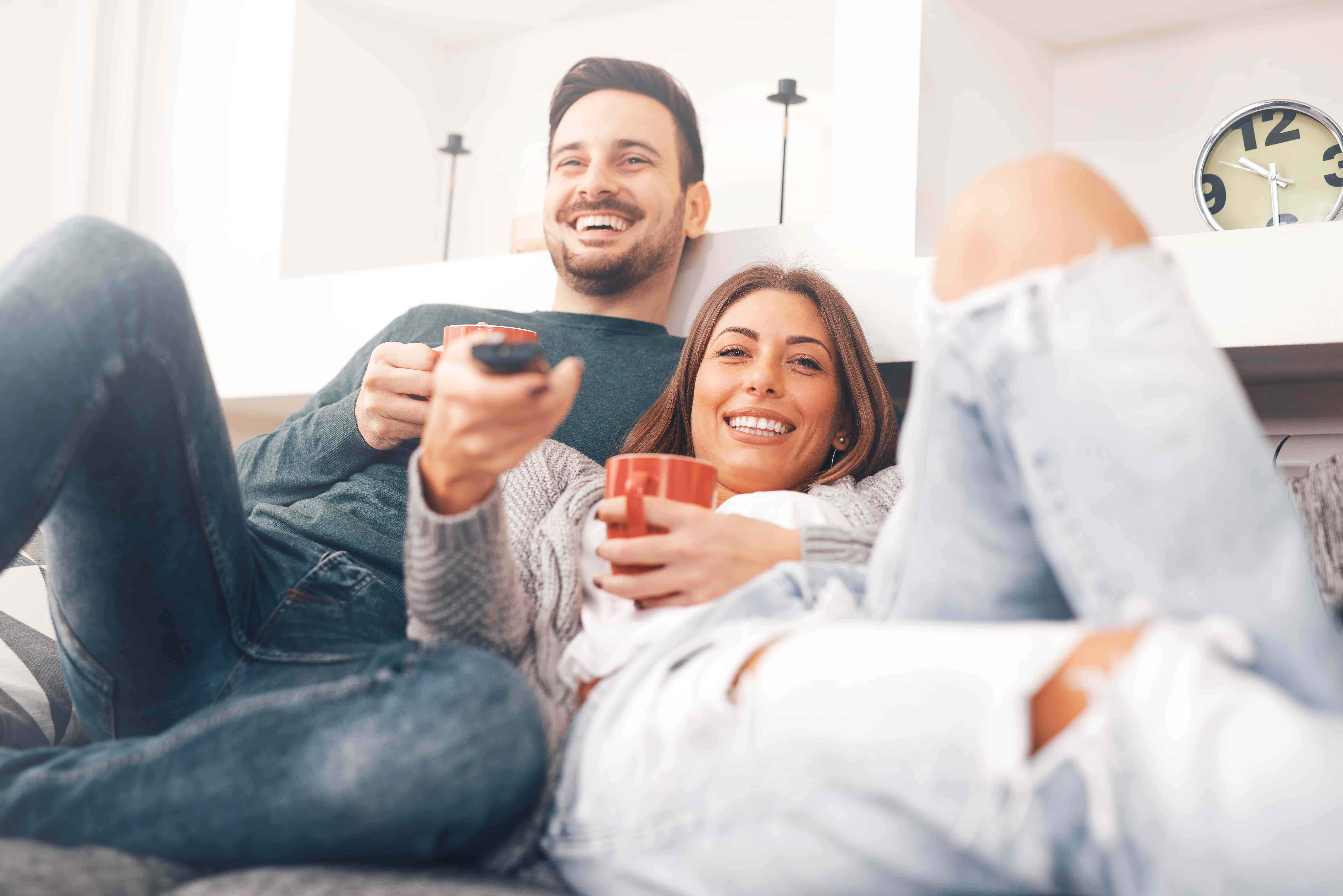 A young couple reclines while smiling on their couch, with remote control poised to choose which TV program to watch
