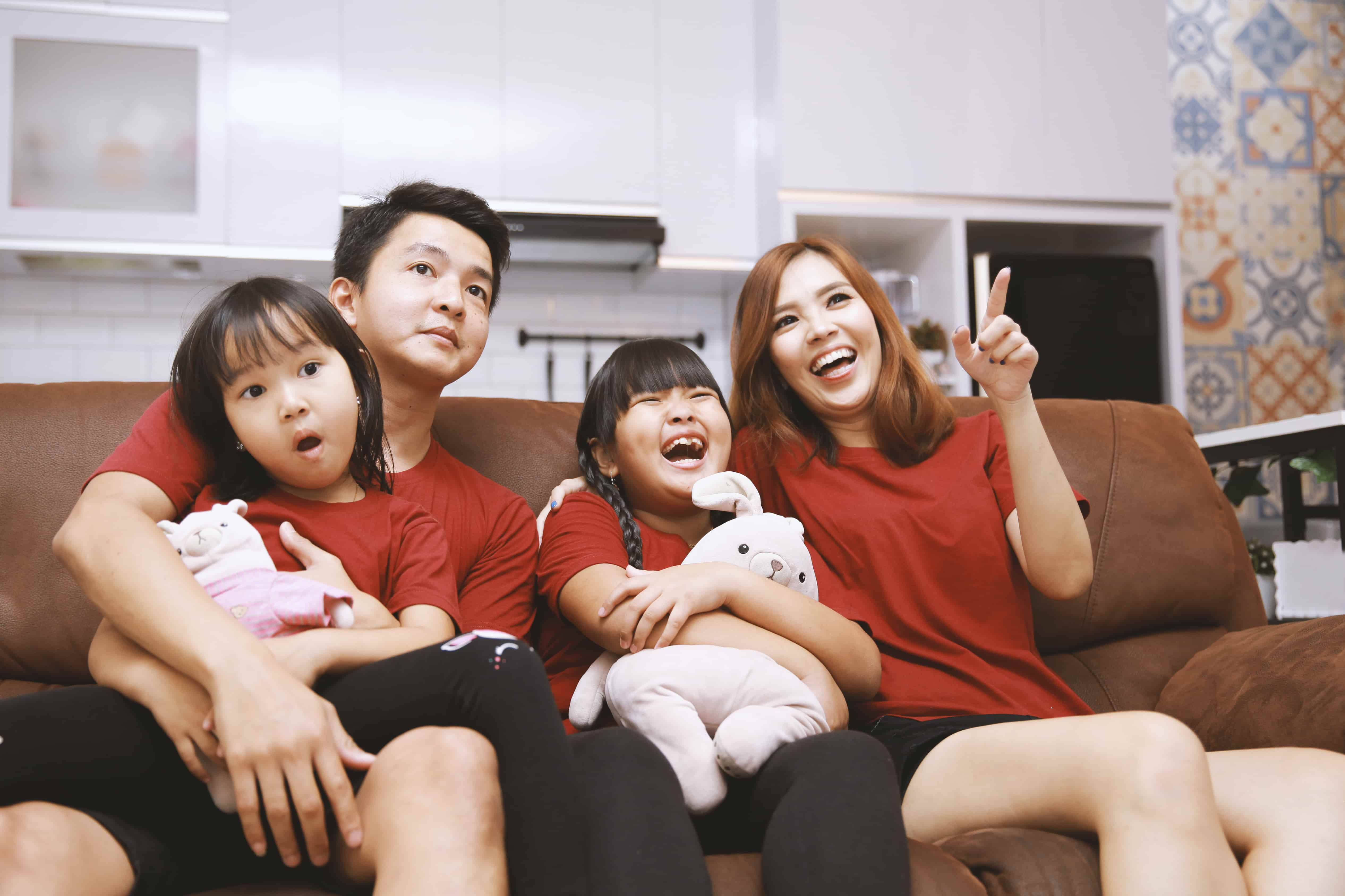 An Asian American family sits on their couch, watching and enjoying a TV program