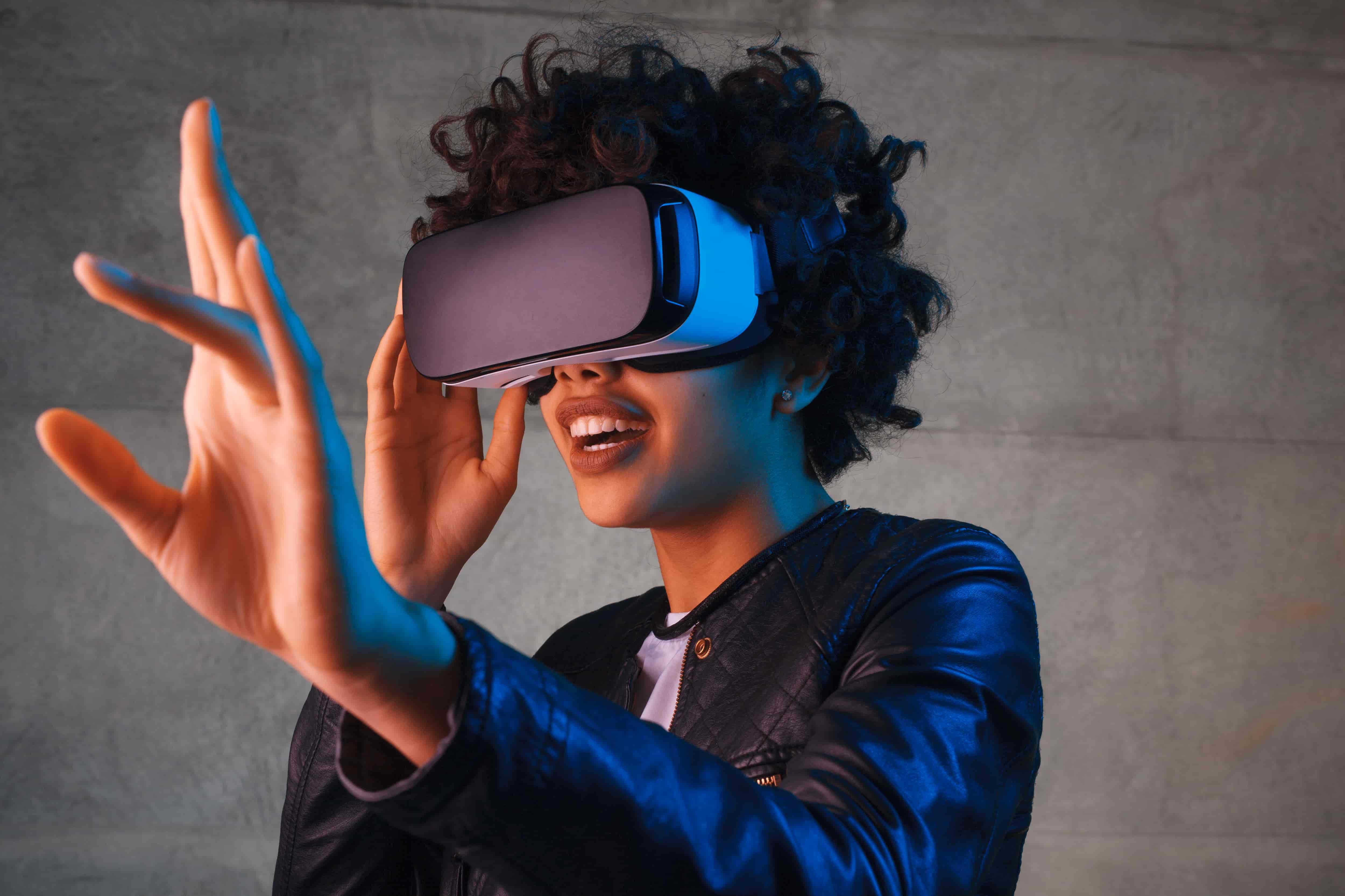 A young African American woman wearing a virtual reality headset holds her hand out in front of her as if touching an unseen object.