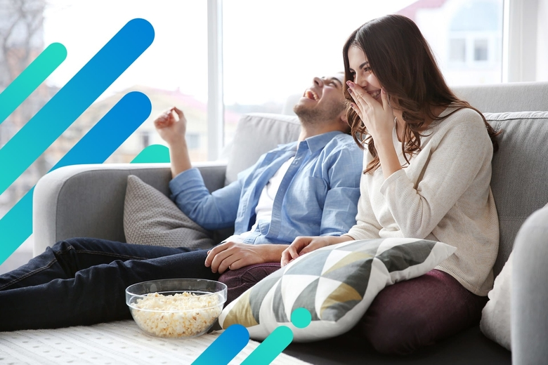 A couple laughs hysterically while relaxing on a sectional couch, watching TV with a bowl of popcorn sitting between them.