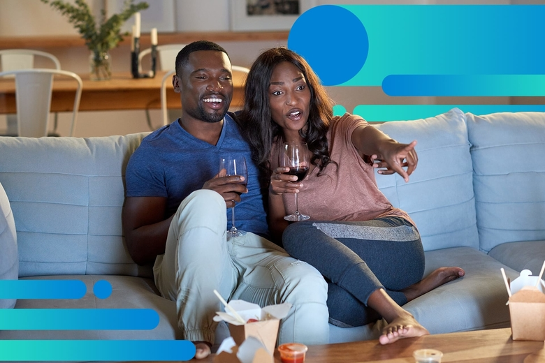 An African American couple smiles while watching a movie on their couch, each is holding a glass of red wine