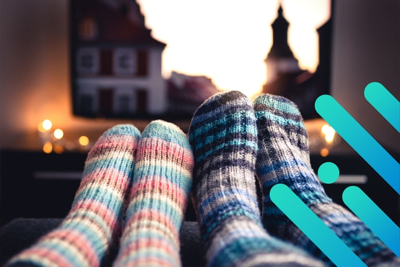 Close-up photograph of two people's feet in warm socks, nestled closely together in the foreground of a living room with a television depicting a sunlit building in the background