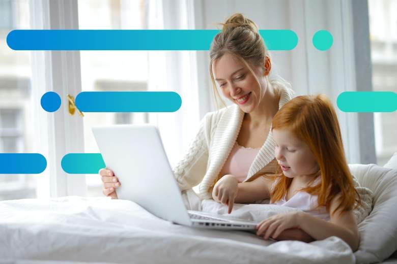 mother and daughter sitting in bed looking for something to watch on a laptop together