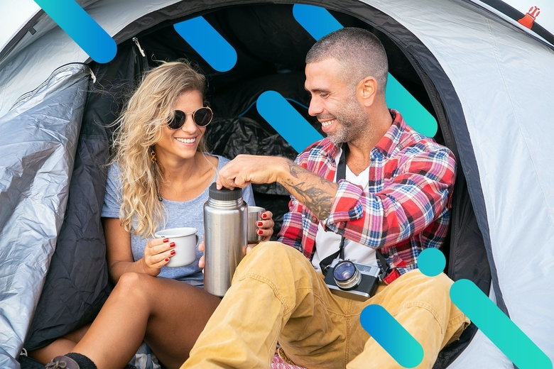 smiling couple camping and enjoying a beverage