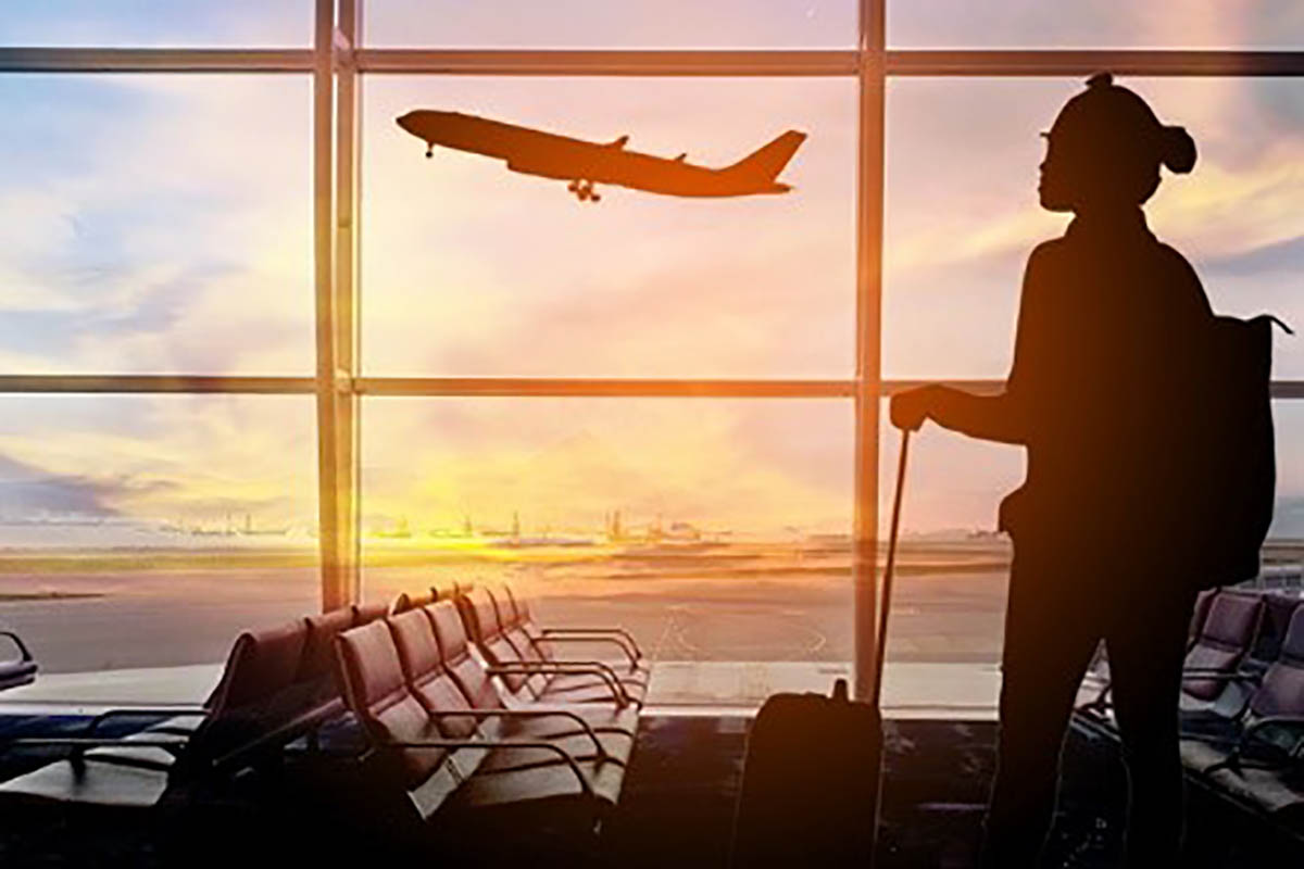 Woman standing with luggage, watching airplane take off through the window