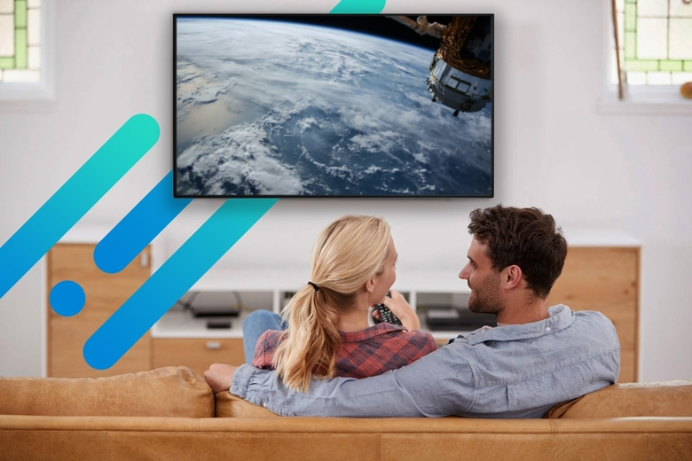 Man and woman streaming space content on large modern screen in living room