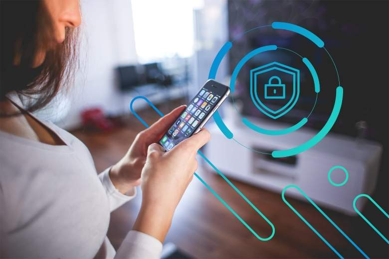 Woman in her living room using her mobile device to activate her smart home security system